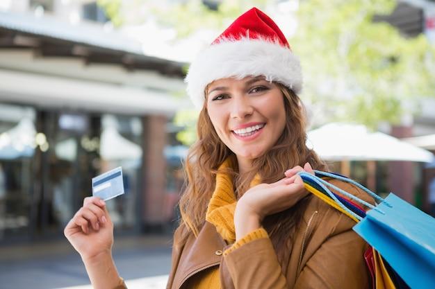 サンタの帽子とショッピングバッグと笑顔の女性の肖像画