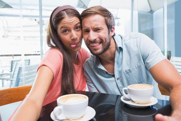 奇妙な顔とセルフを作る若いカップル