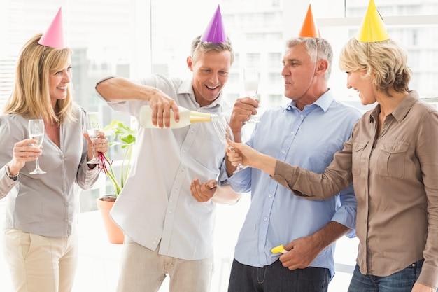 誕生日の乾杯を作るカジュアルなビジネスマン