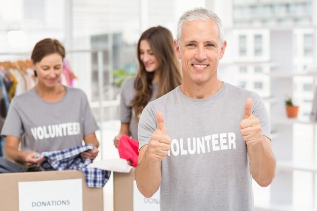 Улыбающийся волонтер, делающий большие пальцы