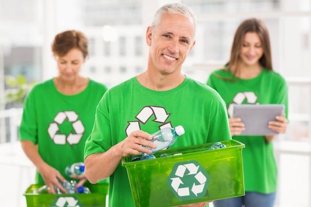 リサイクルボックスを持っている笑顔のエコマインドマン