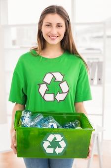 リサイクルボックスを持っている笑顔のエコなブルネット