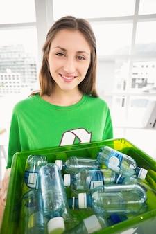 リサイクルボックスを見せている笑顔のエコマインドブルネット