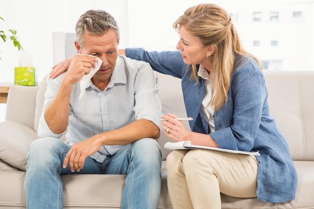 心配したセラピスト慰めの泣いている男性患者