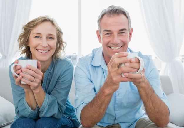 コーヒーを持っているソファーに座っている笑顔の中世の恋人