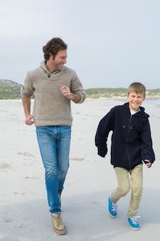 ビーチでジョギングする若い男と息子