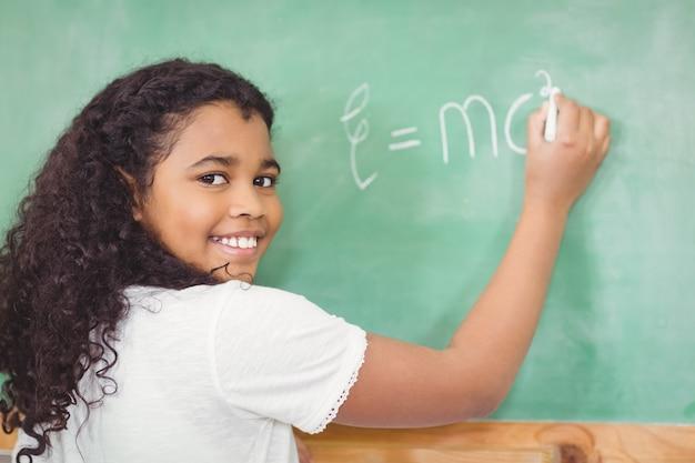 生徒が教室での黒板に笑顔を描く