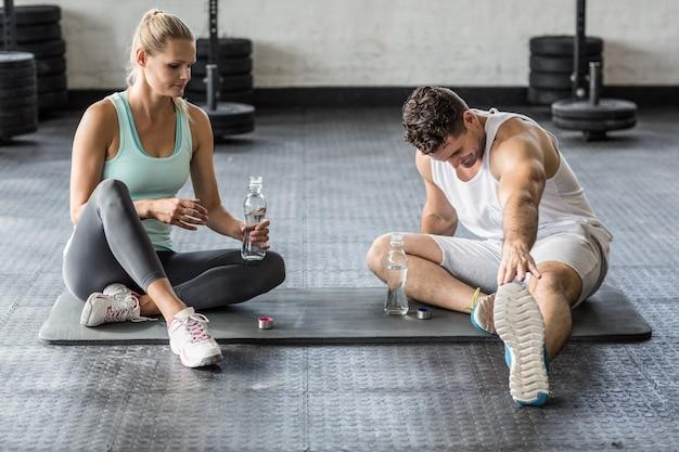 ストレッチと水を飲むスポーツカップル