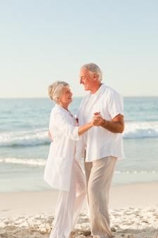 ビーチで踊っている高齢者のカップル