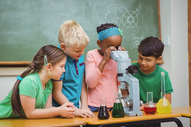 科学ビーカーと顕微鏡を使用している学生