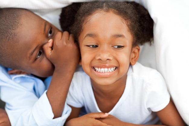 Этнический маленький мальчик что-то шепчет своей сестре