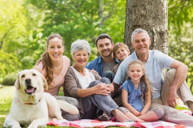 ペットの犬が公園に座っている拡大家族
