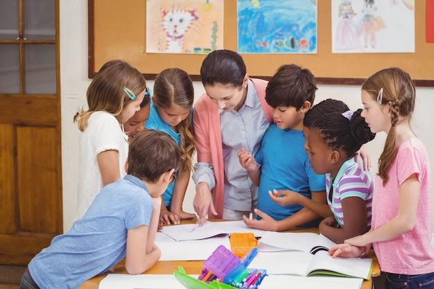 教師と生徒は一緒に机で働いています