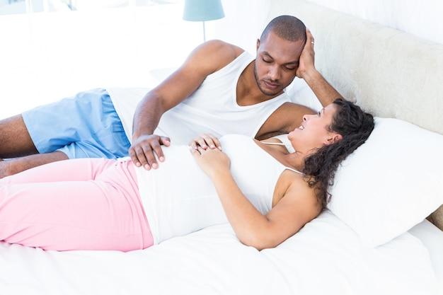 Счастливая беременная жена отдыха с мужем на кровати