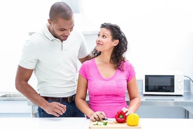 野菜をチョッピングしながら夫を見て妊娠中の妻