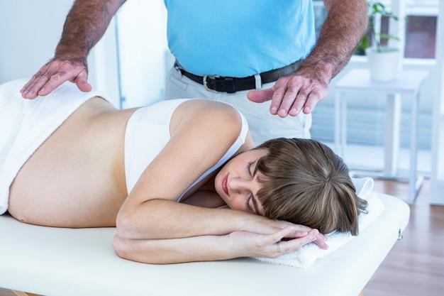 妊婦にレイキをする男性セラピスト