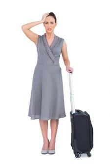 スーツケースのポーズが付いていると心配していた豪華な女性