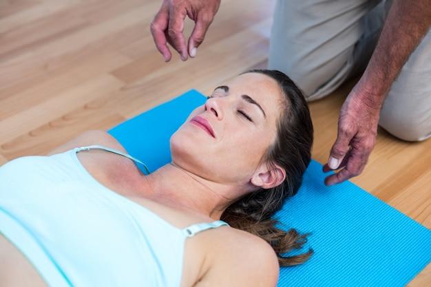 マットの上に横たわっているリラックスした妊婦の高い角度の光景