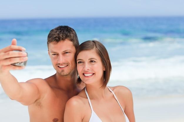 ビーチにカメラを持っている恋人たち