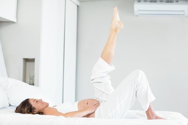 ベッドで脚を持つ幸せな女性