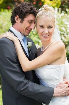 お互いを抱き合っているロマンチックな魅力的な新婚カップル