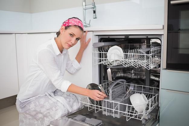 Серьезная очаровательная женщина с помощью посудомоечной машины