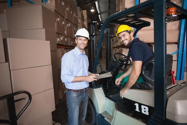 Менеджер склада разговаривает с драйвером вилочного погрузчика