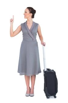 彼女の指を指すスーツケースと陽気な豪華な女性