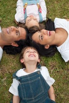 かわいい子供たちとその両親が芝生に横たわっている