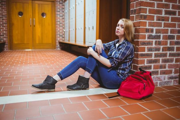 壁に床に座っている心配している学生