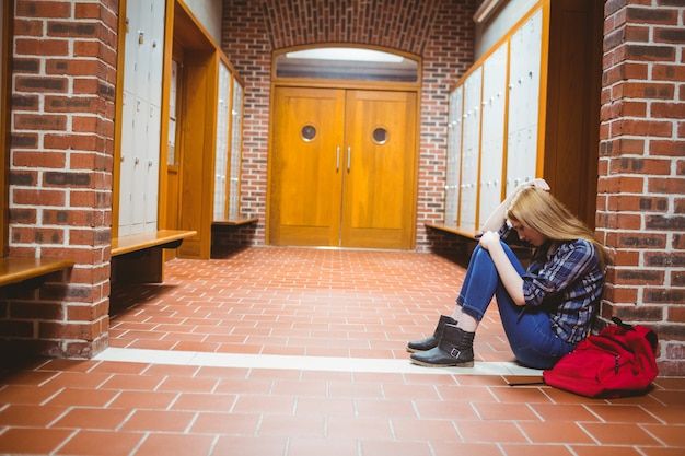 壁の上に床に座っている慎重な学生