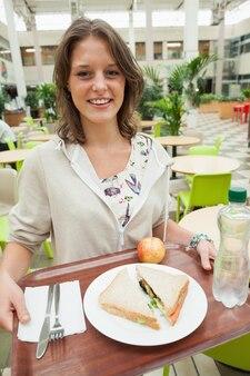 Студентка с подносом для еды в столовой