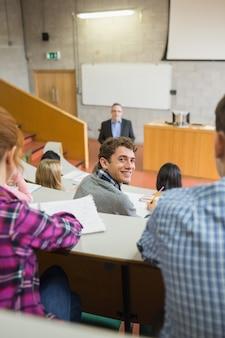 Улыбающийся мужчина со студентами и преподавателем в лекционном зале