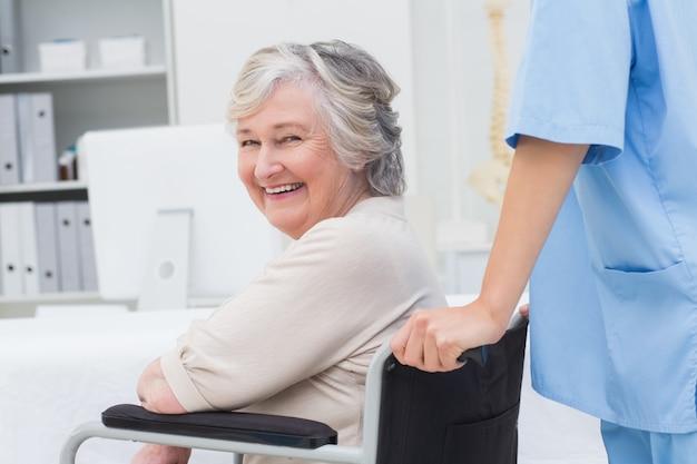 Старший пациент в инвалидной коляске выталкивается медсестрой