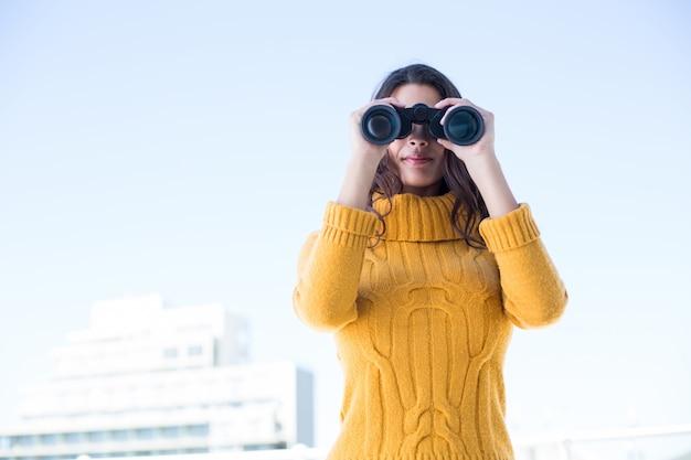 双眼鏡で見ている美しい女性