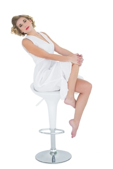 豪華なファッションブロンドのモデルは、バーの椅子に座ってポーズ