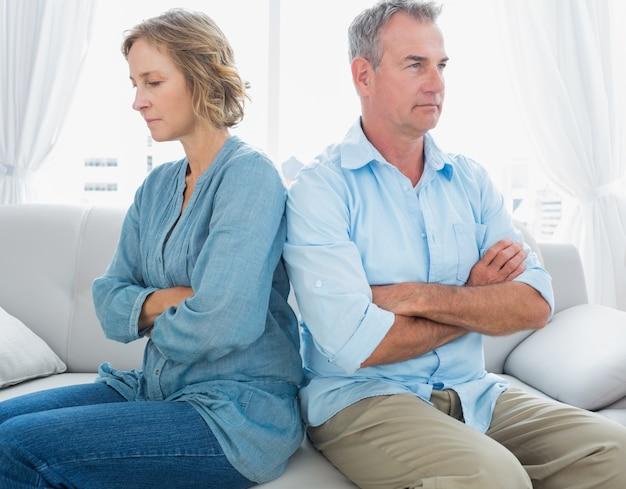 中年のカップルは、戦いの後に話していないソファに座って