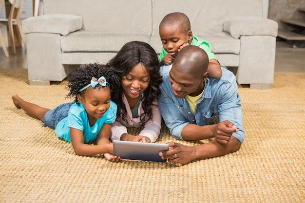Счастливая семья, лежа на полу с помощью планшета