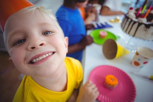 Возбужденный ребенок, наслаждающийся вечеринкой по случаю дня рождения