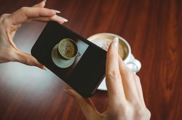 彼女のコーヒーの写真を撮っている女性