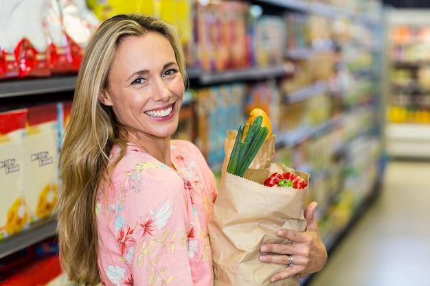 美しい女性は、食料品の袋で立って