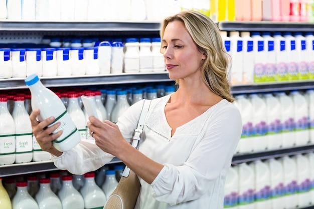 ミルクボトルの写真を撮っている美しい女性