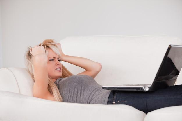 Привлекательная белокурая женщина расстроена своим компьютером, лежащим на диване