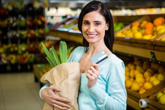 クレジットカード、食料品袋を持っている笑顔の女性