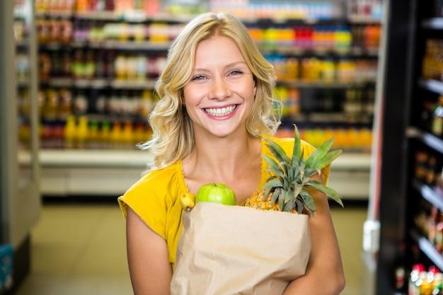 食器袋で通路に立っている笑顔の女性