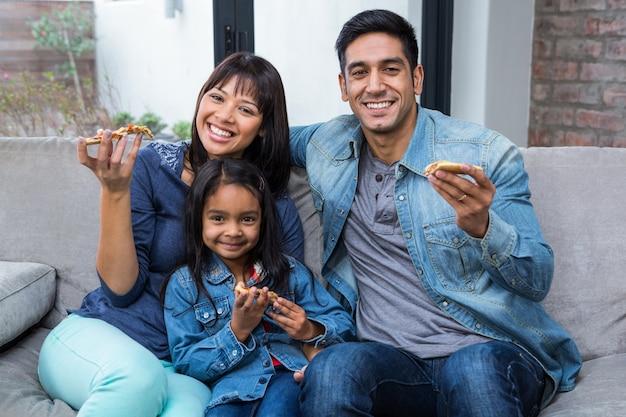 ソファで家族が食べる笑顔のピザ