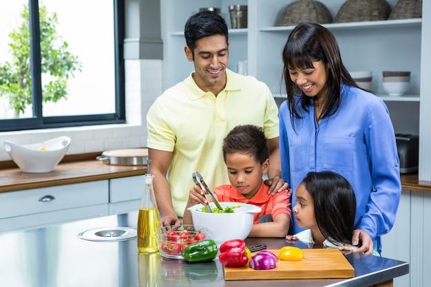 キッチンにサラダを準備する幸せな家族