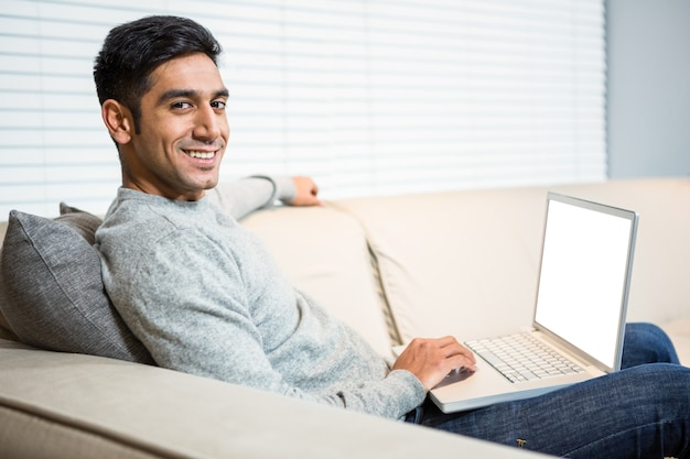 ソファでラップトップを使用しているハンサムな男
