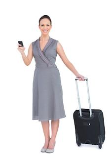 彼女のスーツケースの文字メッセージで陽気な豪華な女性
