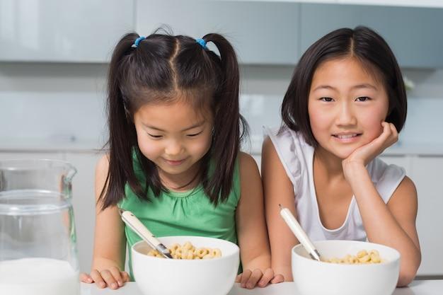 二つの笑顔の若い女の子が台所に座って座って